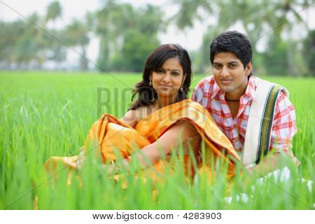 Young Couple Sitting In A Paddy Field