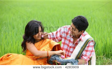 an asian couple in the paddy field having breakfast poster
