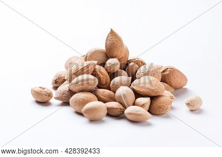 Almonds With Shell, Prunus Amygdalus Heaped On White Background