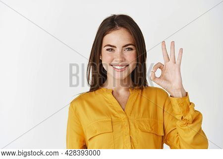 Young Confident Woman Smiling, Showing Okay Gesture, Saying Yes Or Alright And Standing On White Bac
