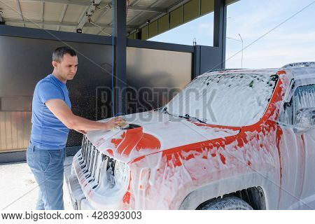 A Man Washes A Car With A Sponge At A Car Wash. Car In The Foam Outdoors