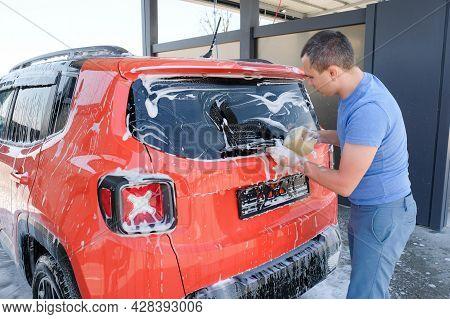 A Man Washing A Car With Soap, Car Wash. Car In Foam