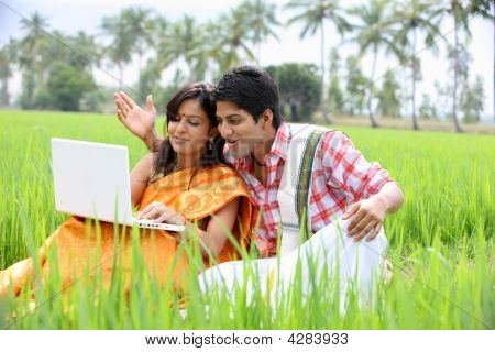 Couple Sitting In The Paddy Field With Their Laptop