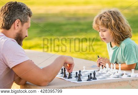 Spending Time Together. Strategic And Tactic. Tutorship. Dad And Kid Play Logic Game.