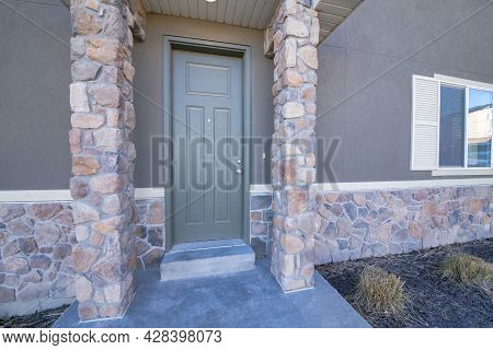Gray Front Door Exterior With Stone Wall Siding And Column Posts