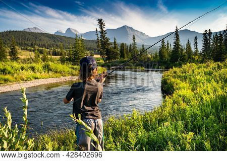 A Young Child Casting His Fishing Rod Into The Crossest River With A Rocky Mountain Backdrop In Sout