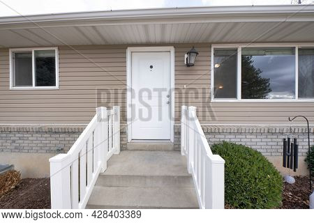 Front Door Exterior Of A House With Vinyl Wood And Bricks Sidings