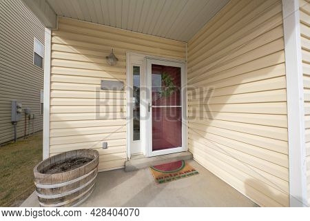 Exterior Of A House Entrance With A Vinyl Wood Siding And A View Of A Lawn On The Left