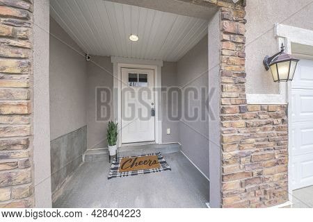 Front Door Exterior With Potted Plants And Decorative Doormat At The Doorsteps