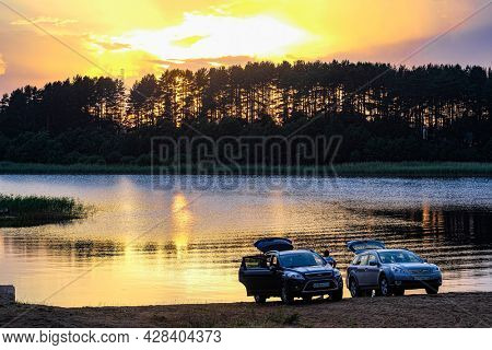 Tver oblast, Russia - June, 25, 2021: Cars on a bank of Seliger lake in Tver oblast, Russia at sunset