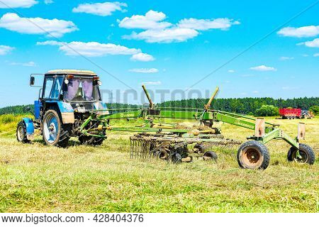 Moscow oblast, Russia - July, 9, 2021: Tractor  works on a field in Moscow oblast, Russia
