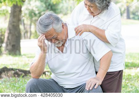 Senior Male Asian Suffering In A Forest , Headache High Blood Pressure At Garden Park , Wife Support