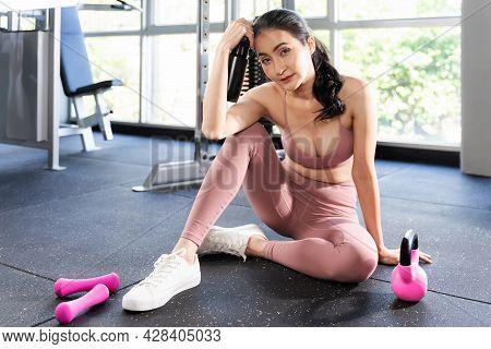 Beautiful Fitness Slim Fit Woman In Sportswear Sitting Take A Break In A Gym Room , Asian Sexy Girl