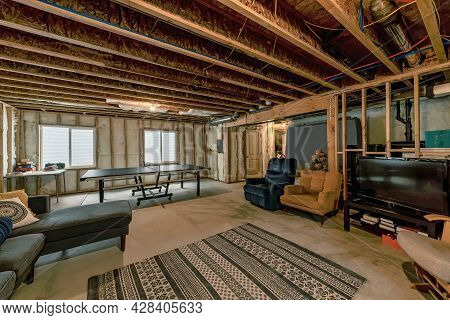 Lounge Inside An Unfinished Basement With Wooden Beams And Wall Insulation