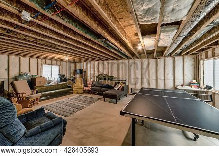 Unfinished Basement Interior With Wooden Beam And Posts