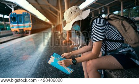 New Normal Traveler Concepts. Young Female Tourist Wearing A Mask Looks At A Tourist Map While Waiti