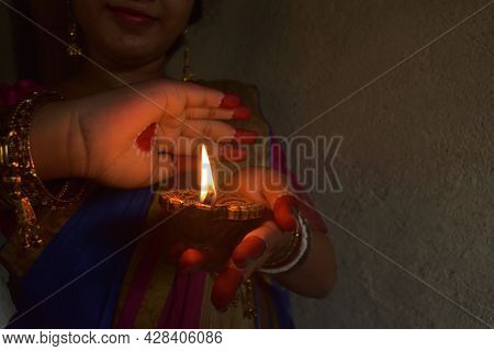 An Indian Woman Devotee Lights Lamps And Celebrated The Diwali Or Deepavali Festival. Concept Of The