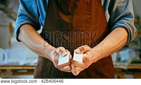 Young man in apron holding a piece of stone close-up. Male hands demonstrating a piece of blue glass