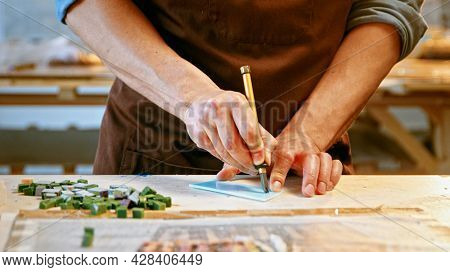 Male hands cutting a piece of glass in creative workshop close-up