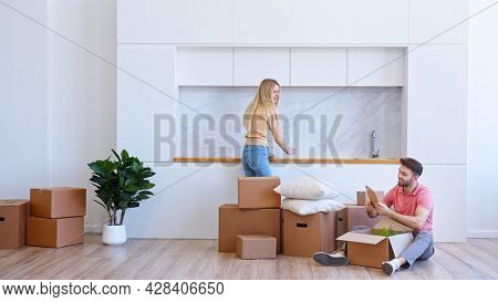 Young woman blonde with long loose hair helps bearded man unpack brown cardboard box in new apartment after relocation to house