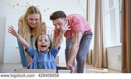 Joyful parents play with little funny daughter in blue dress moving kid along new apartment floor in large brown cardboard box