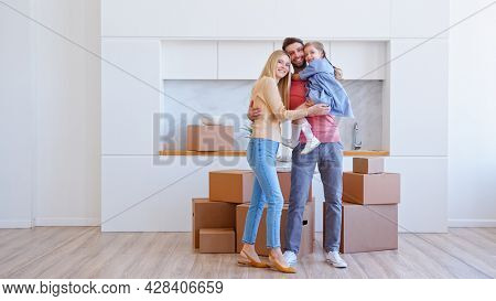 Little funny preschooler girl brings cardboard box on large pile and jumps in bearded father arms near mother in new flat