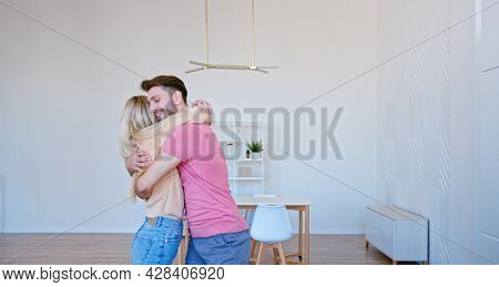 Romantic newlyweds with large brown cardboard boxes put things on floor pile in new apartment and give high five with joyful smiles