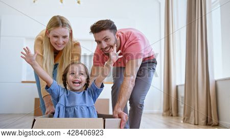 Funny parents lady blonde and bearded guy move large cardboard box with delighted preschooler girl along new apartment floor