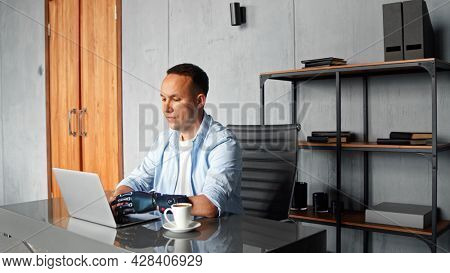 Concentrated man hacker with black bio hand prothesis types on grey laptop sitting at table with cup of coffee in home room