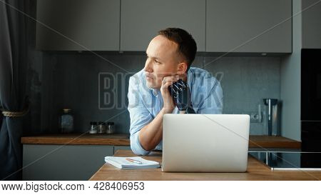Freelancer man employee with bio hand prothesis sits at table with notes and laptop and look outside window solving problem at home remote work