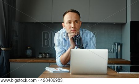 Company manager cyborg guy with artificial hand prothesis sits at table with notes in notebook and laptop solving problem at home