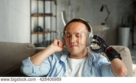 Disabled man with high temple and artificial hand prothesis listens to favourite track in wireless earphones with happy smile at home closeup