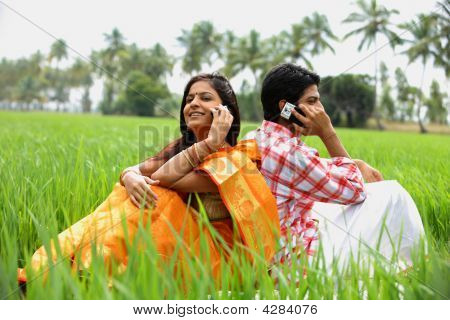 Couple Sitting In Paddy Field Talking On Their Cell Phone