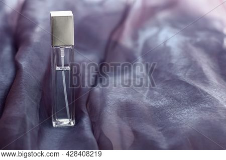A Long Faceted Bottle Of Liquid Stands On The Fabric. Elongated Glass Vial. The Fabric Is Wrinkled.