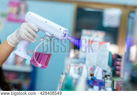 Close Up Hand Of Staff Wearing Gloves Using Electric Alcohol Nano Spray Gun Handheld Blue Light Disi