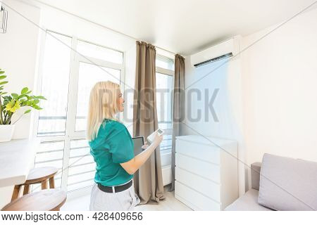 Young Happy Woman Holding Remote Control Air Conditioner In House.