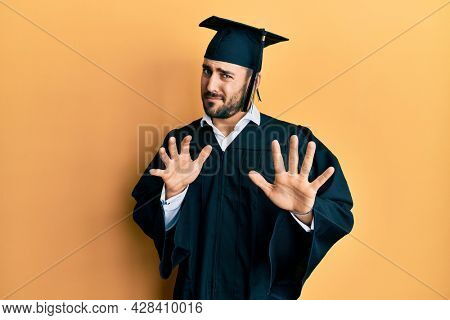 Young hispanic man wearing graduation cap and ceremony robe disgusted expression, displeased and fearful doing disgust face because aversion reaction. with hands raised