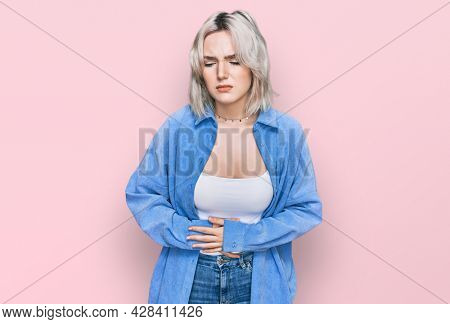 Young blonde girl wearing casual clothes with hand on stomach because indigestion, painful illness feeling unwell. ache concept.