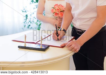Hands Of The Bride And Groom Sign Documents In The Registry Office Close-up.