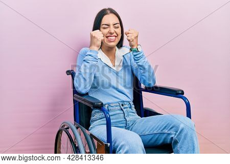 Beautiful woman with blue eyes sitting on wheelchair excited for success with arms raised and eyes closed celebrating victory smiling. winner concept.