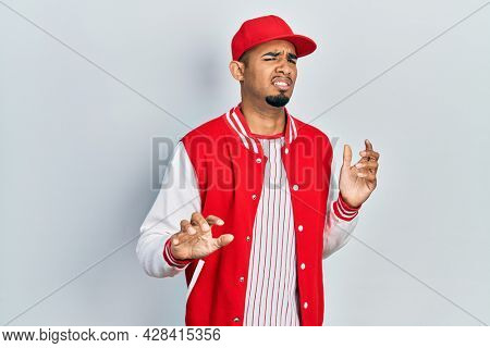 Young african american man wearing baseball uniform disgusted expression, displeased and fearful doing disgust face because aversion reaction. with hands raised