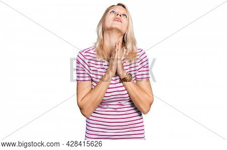 Young caucasian woman wearing casual clothes begging and praying with hands together with hope expression on face very emotional and worried. begging.