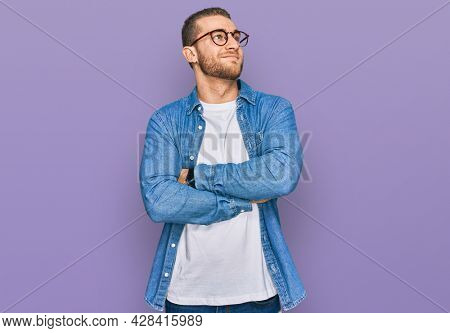 Young caucasian man wearing casual clothes looking to the side with arms crossed convinced and confident