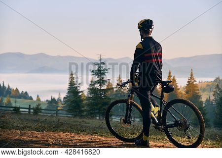 Back View Of Male Cyclist In Cycling Suit Standing With Bike In The Morning. Man Bicyclist Wearing S