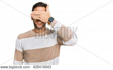 Handsome man with beard wearing casual clothes and glasses smiling and laughing with hand on face covering eyes for surprise. blind concept.