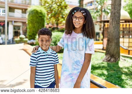 African american brother and sister smiling happy outdoors. Black family of two siblings at the city on a sunny day.
