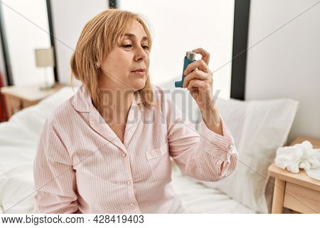 Middle age asthmatic woman using inhaler sitting on the bed at home.