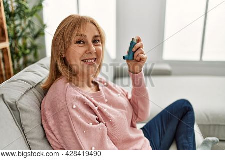 Middle age asthmatic woman smiling happy using inhaler sitting on the sofa at home.