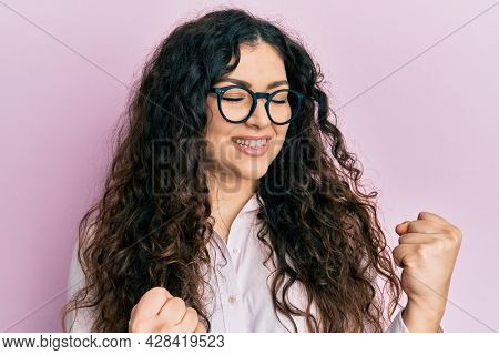 Young brunette woman with curly hair wearing casual clothes and glasses excited for success with arms raised and eyes closed celebrating victory smiling. winner concept.