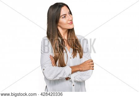 Young beautiful woman wearing casual clothes looking to the side with arms crossed convinced and confident